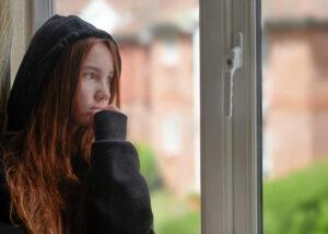 Una ragazza adolescente chiusa in casa guarda fuori malinconica a causa della pandemic fatigue