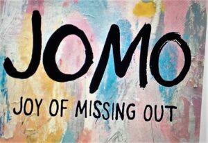 Sfondo colorato e scritta nera JOMO acronimo di joy of missing out, la gioia di ignorare consapevolmente le cose negative