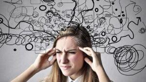 Una donna con le mani alle tempie e gli occhi stretti per lo stress causato dall'ingorgo cognitivo ed emotivo