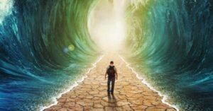 Un giovane di spalle cammina in un tunnel, vedendone la luce al fondo, con i piedi all'asciutto ma due muri d'acqua a destra e a sinistra