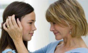 Una mamma guarda negli occhi la figlia adolescente accarezzandole i capelli