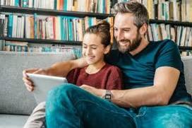 Un papà e una figlia adolescente sorridenti leggono insieme seduti sul divano
